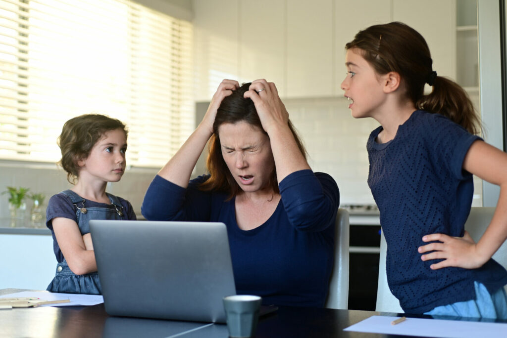 Mother-with-hands-on-head-frustrated-at-two-daughters-arguing-chronic-stress