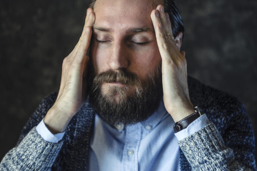 Man-with-hands-on-forehead-with-migraine-headache