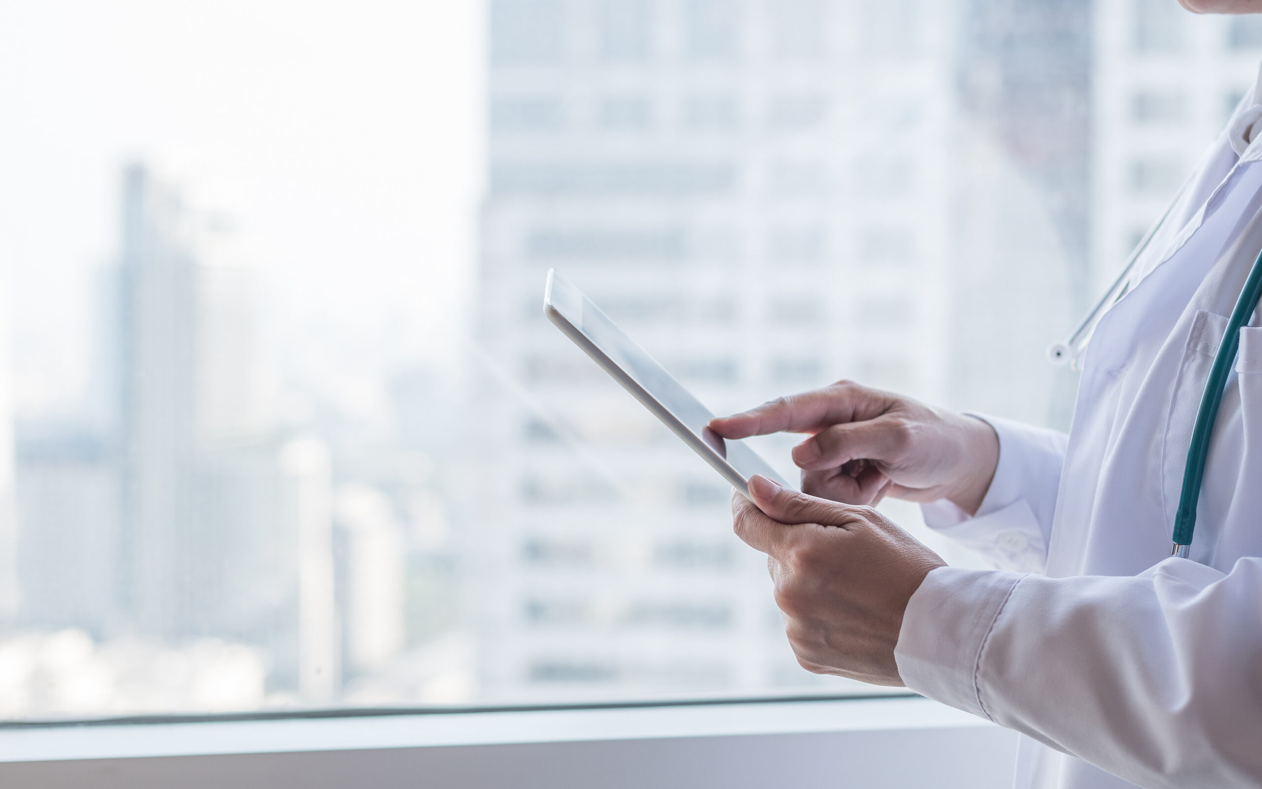 Functional-medicine-doctor-standing-by-the-window-with-tablet